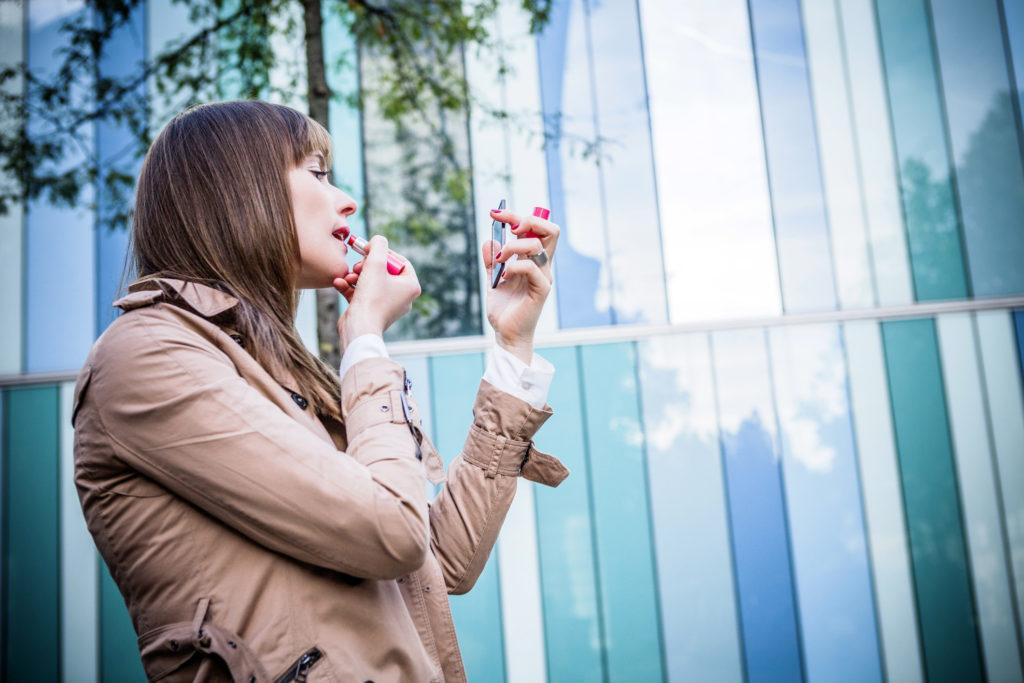 Young woman applying red lipstick, Munich, Bavaria, Germany