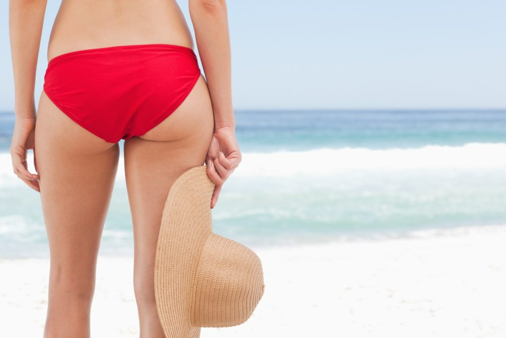 Woman in a red bikini holding a hat against her right leg by the seaside, Image: 138563691, License: Royalty-free, Restrictions: , Model Release: yes, Credit line: Profimedia, Wavebreak