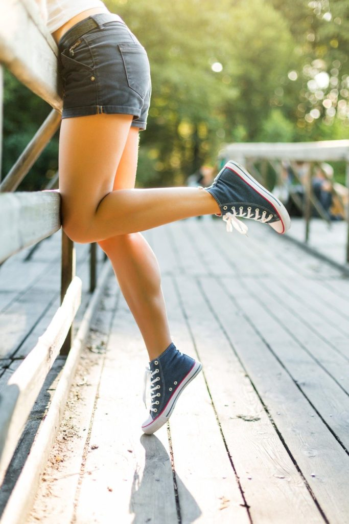 Young woman with beautiful sporty legs leaning on a wooden bridge railing in jeans sneakers
