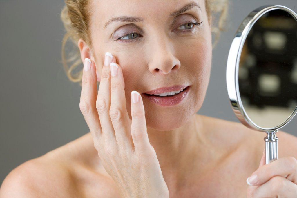 A middle-aged woman looking at her face in the mirror